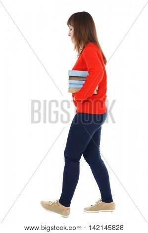 Girl comes with  stack of books. side view. Rear view people collection.  backside view of person.  Isolated over white background. Thoughtful girl in a turquoise jacket carries a stack of books.