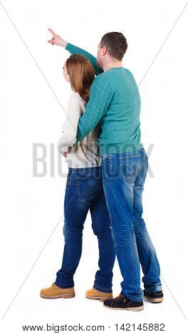 young couple pointing at wal Back view  (woman and man). Rear view people collection.  backside view of person.  Isolated over white background. A man in a green jacket hugged from behind the woman