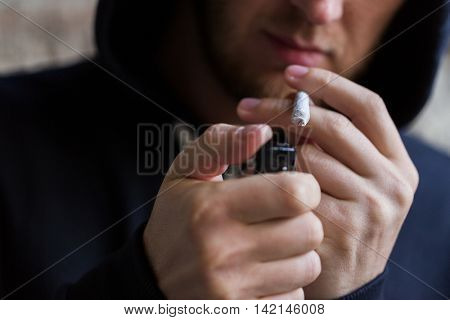 drug use, substance abuse, addiction, people and smoking concept - close up of addict lighting up marijuana joint with lighter