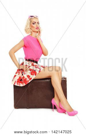 Beautiful sexy blonde pin-up girl in mini skirt and hot pink shoes sitting on big vintage bag over white background
