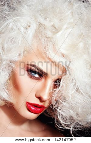 Close-up portrait of young beautiful woman with platinum blonde curly hair and red lipstick