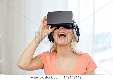 technology, virtual reality, cyberspace, entertainment and people concept - happy amazed young woman in virtual reality headset or 3d glasses and headphones at home