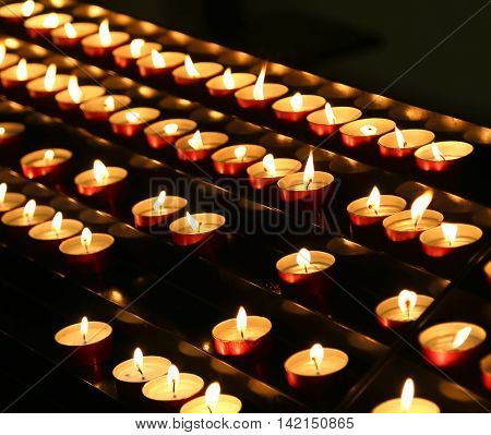 Many Candles Lit With Flickering Flame In The Place Of Prayer