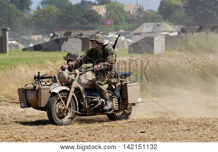 WESTERNHANGER, UK - JULY 20: A motorcycle and sidecar team head around a dusty main arena during a public performance at the War & Peace Revival show on July 20, 2016 in Westernhanger