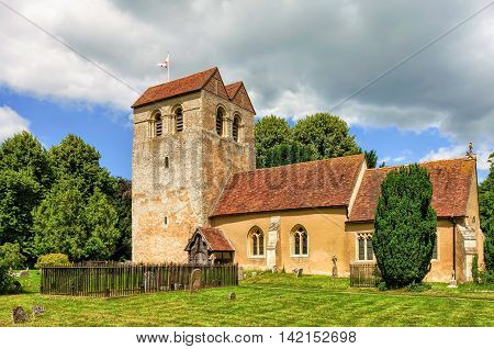 Parish church of St. Bartholomew in Fingest village of Buckinghamshire, England with blue skies and grey clouds.