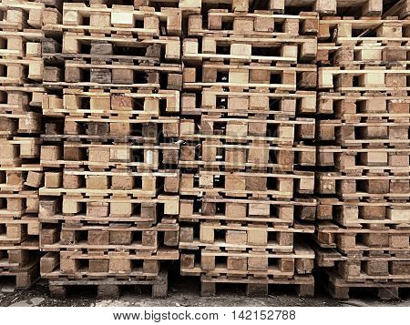 Used wooden shipping pallets stocked in warehouse of logistic company