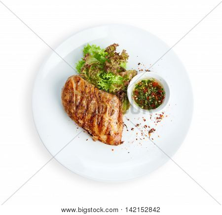 Restaurant food - chicken fillet grilled steak isolated on white background. Big piece of meat with lettuce on white round plate top view