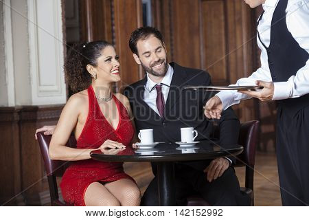 Cropped Image Of Waiter Serving Coffee To Couple