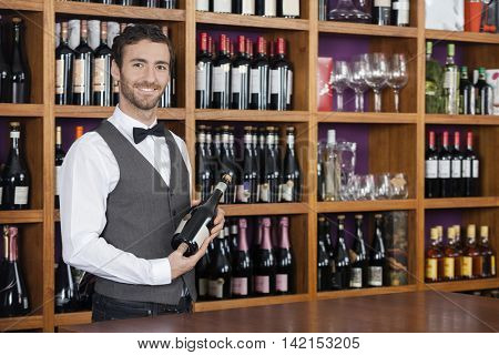 Confident Bartender Holding Red Wine Bottle At Counter