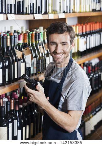 Confident Salesman Arranging Wine Bottle On Shelf