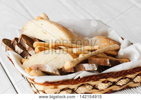 Rectangular dish with bread and breadsticks on white wooden background. Bakery products variety served in wicker basket
