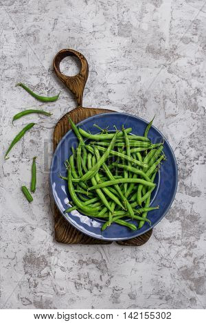 French bean in blue plate on old wooden board on the rough light gray surface top view