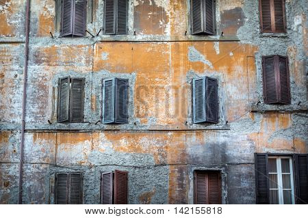 Worn out building with window shutters in decay, Rome Italy.