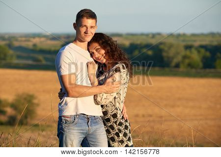 happy young couple posing high on country outdoor, romantic people concept, summer season