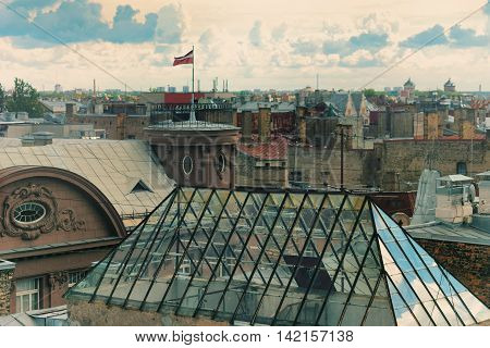 The roofs of the city of Riga with Latvian national flag and glass windows