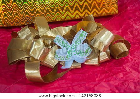 image of gold bow with white bow on red wrinkled paper