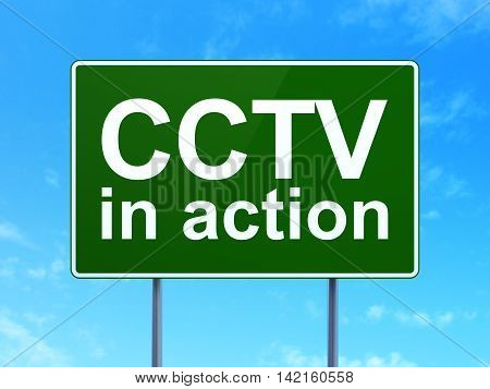 Protection concept: CCTV In action on green road highway sign, clear blue sky background, 3D rendering