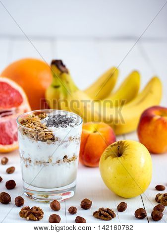 Healthy breakfast: yogurt with muesli and chia seeds, fruits and nuts on white wooden background. Dieting, healthy lifestyle concept meal. Vertical with copyspace