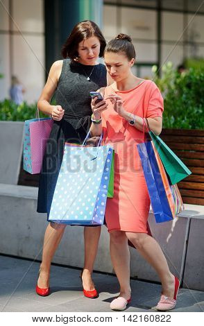 Two young women standing near the Mall. They handle many multicoloured packages with purchases. Women thoughtfully look at the screen of a mobile phone.