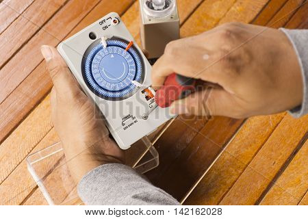 Timer tool with screwdriver in hand of man cleaning on wooden background.