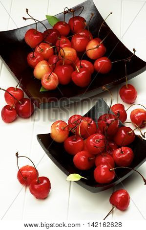 Fresh Ripe Sweet Maraschino Cherries in Two Black Wooden Plates closeup on Plank White background. Focus on Foreground