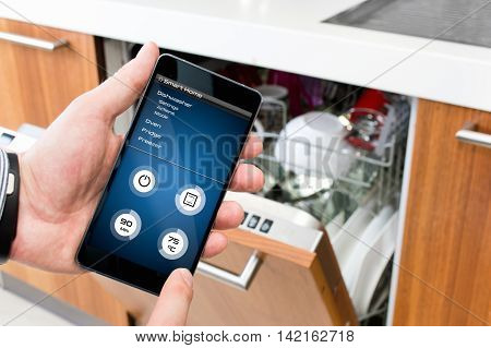 Man turns on the dishwasher by smartphone application.
