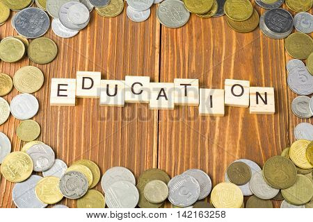 Education text on wooden cube with coins frame at wood background.