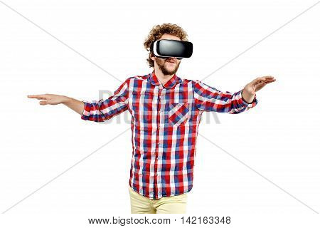 Young curly-haired man in plaid shirt using a VR headset and experiencing virtual reality isolated on white background