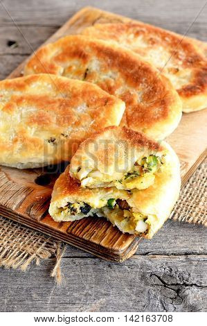 Fried pies with mushrooms, eggs, green onions and dill on a wooden board. Delicious breakfast, picnic snack idea. Recipe from unleavened dough