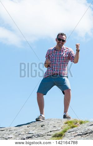 Happy Cheerful Man On Top Of A Climbing Rock