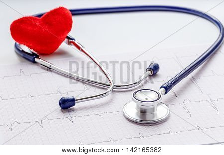 stethoscope on a white background with plush red heart and cardiogram