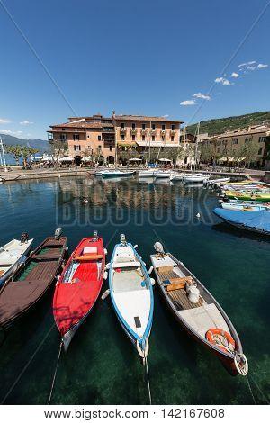 TORRI DEL BENACO - MAY 4, 2016: A row of fishing boats in the small harbor of Torri del Benaco. Garda Lake. Italy
