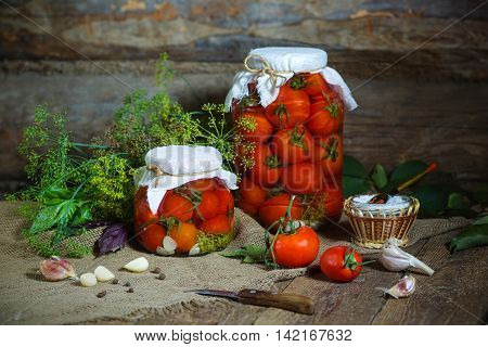 A few jars with canning tomatoes and ingredients for conservation. Rustic style