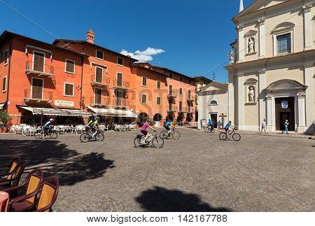 TORRI DEL BENACO - MAY 4, 2016: Cyclists in Torri del Benaco at Garda Lake in Italy