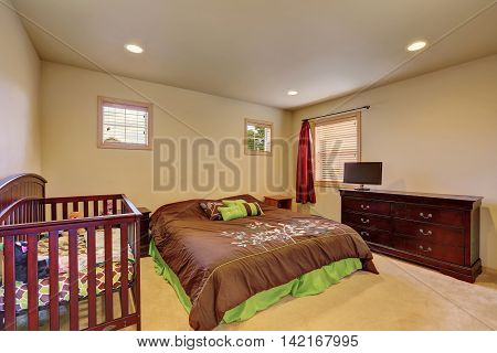 Brown Bedroom With Crib And Vintage Chest Of Drawers.