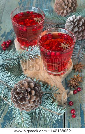 Christmas table: two glasses of red hot mulled wine ore compote (stewed fruit) with spices and cowberries surrounded by fir branches and cones