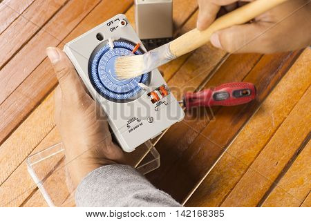 Timer tool with brush in hand of man cleaning on wooden background.