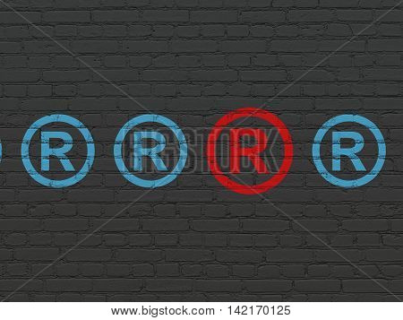 Law concept: row of Painted blue registered icons around red registered icon on Black Brick wall background
