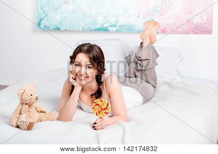 Cute Young Brunette Girl With Two Plaits At Home Pajamas Lying O