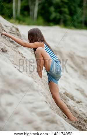 Girl Climbing On The Sand