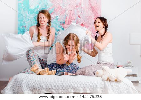 Cheerful Young Girl Fighting Pillows On The Bed At Home