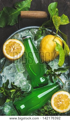 Bottles of green lemonade on chipped ice in metal tray with fresh lemons and mint over dark wooden background, top view, vertical composition