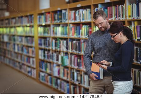 Mature students using digital tablet in college library