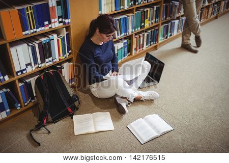Mature student reading a book sitting on the library floor