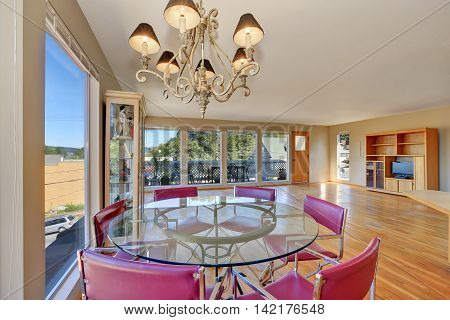 Dining Area With Round Glass Table And Red Chairs