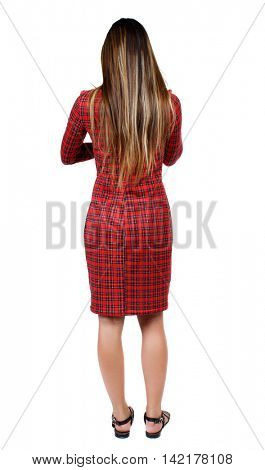 back view of standing young beautiful  woman.  girl  watching. Rear view people collection.  backside view of person. The girl in red plaid dress standing back and looking ahead.