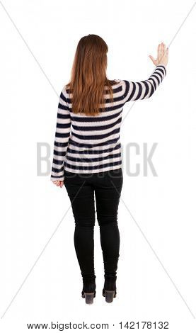 back view of young woman presses down on something. Isolated over white background. Rear view people collection. backside view of person. Girl in a striped sweater hand presses the button.