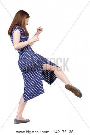 skinny woman funny fights waving his arms and legs. Isolated over white background. The brunette in a blue striped dress has a foot.