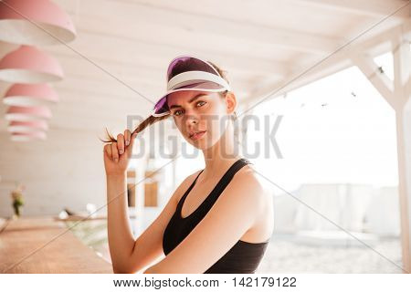 Young beautiful sports woman posing at beach cafe outdoors
