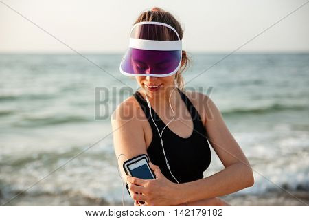 Young fitness runner woman resting on beach listening to music with phone case sport armband strap